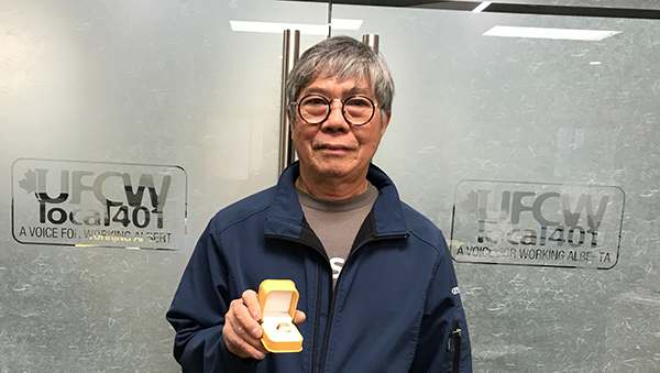 Minh Tran shows off his 401 retirement ring